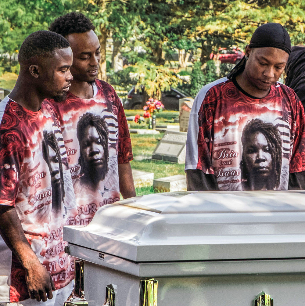 men in memorial shirts surround a casket